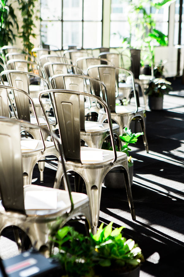 Metal industrial chairs and live plants at a conservatory wedding ceremony at Terra in San Francisco by destination wedding planner Mango Muse Events