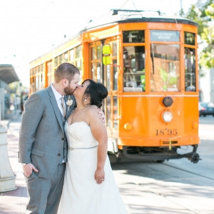 Bride and groom sharing a kiss in front of a cable car in San Francisco by destination wedding planner Mango Muse Events