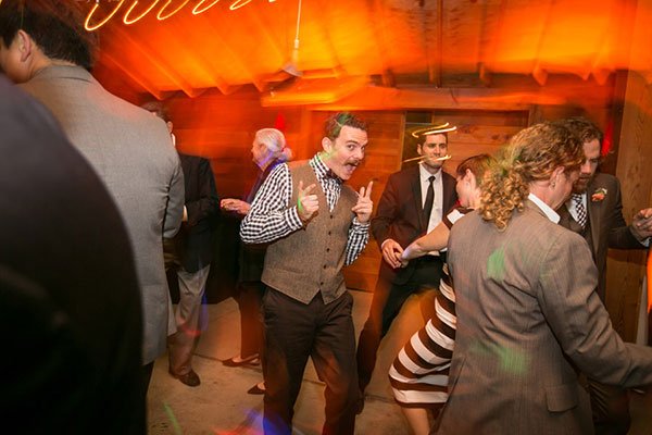 Happy wedding guests having fun dancing at a barn wedding by Destination wedding planner Mango Muse Events