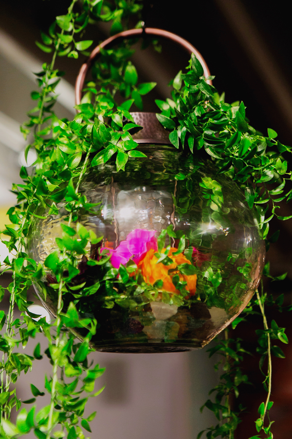 Hanging lantern with greenery, florals and collected beach glass for a eclectic global boho wedding table design for Pottery Barn by destination wedding planner Mango Muse Events
