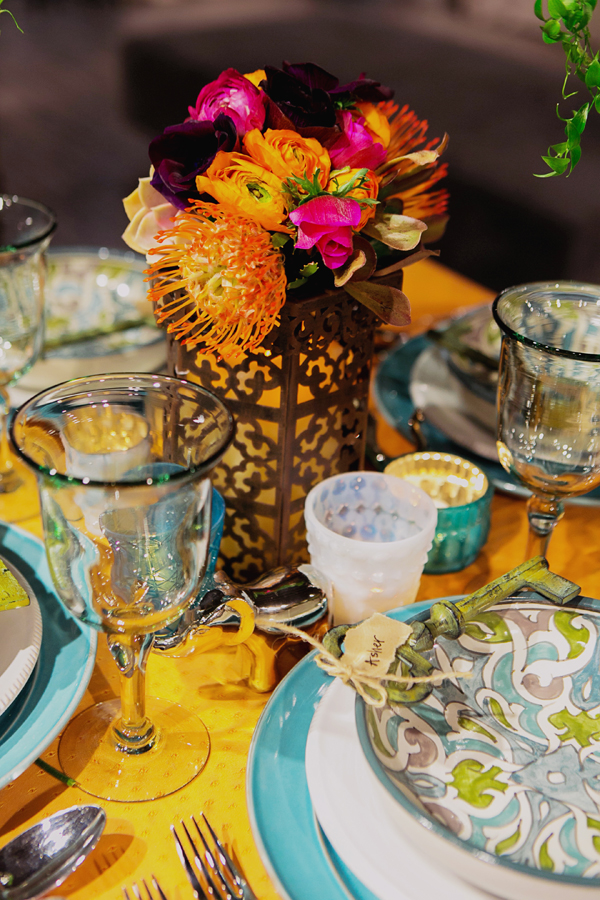 Mixed colored votives and animal figurines as a part of the centerpiece for an eclectic global bohemian wedding table design for Pottery Barn by destination wedding planner Mango Muse Events