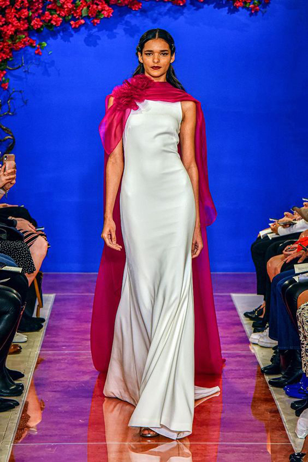 Sleek wedding dress with a red cape by Theia bridal fall 2020 wedding dress trend picked by destination wedding planner Mango Muse Events