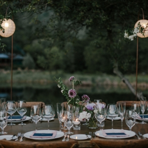 Wedding reception table floral centerpieces and lighting design for a Calistoga Ranch lake wedding by destination wedding planner Mango Muse Events