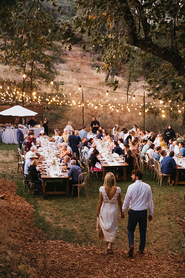 Alfresco wedding reception dinner with bistro lights at Autocamp Yosemite by destination wedding planner Mango Muse Events