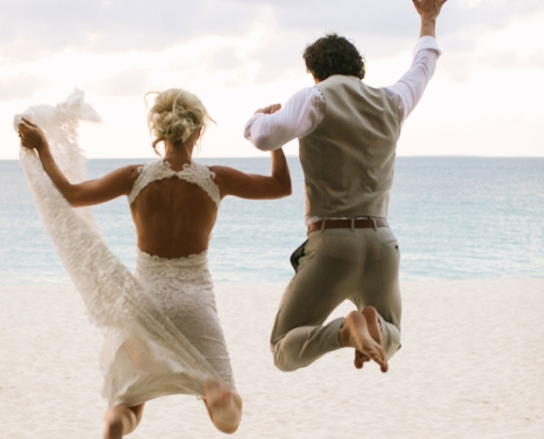 Newlyweds jumping for joy at their Caribbean destination wedding in Anguilla by destination wedding planner Mango Muse Events