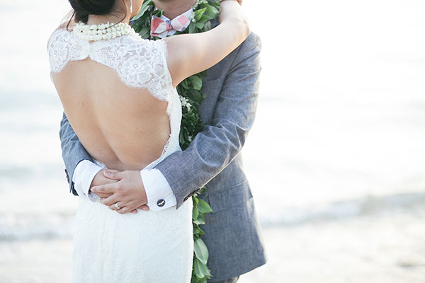 Bride and groom hugging at their beach wedding in Hawaii by destination wedding planner Mango Muse Events