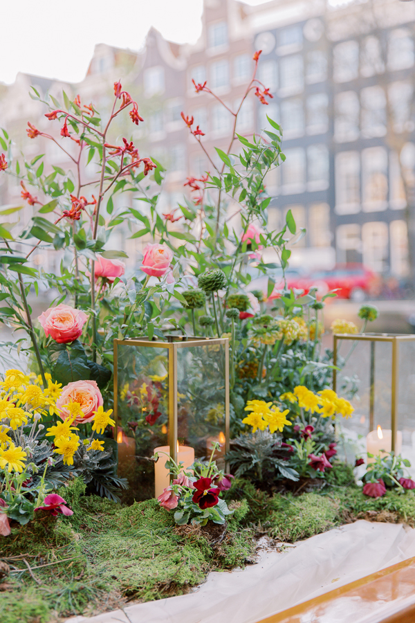 Lanterns and flowers create a garden on a canal boat for a wedding in Amsterdam by destination wedding planner Mango Muse Events