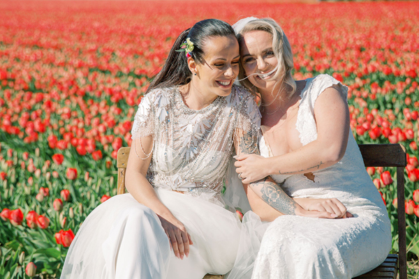 Happy brides at their same sex wedding ceremony in the tulip fields in Holland by destination wedding planner Mango Muse Events