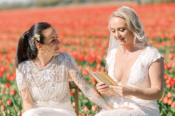 Bride reading personal vows at a same sex wedding ceremony in the tulip fields in the Netherlands by destination wedding planner Mango Muse Events