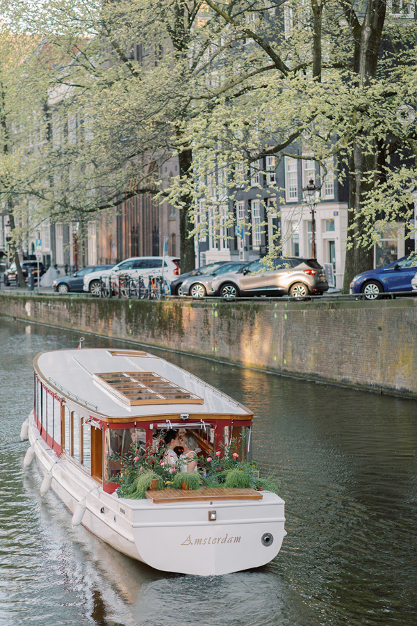 Wedding boat kiss at a lesbian wedding in Amsterdam by destination wedding planner Mango Muse Events