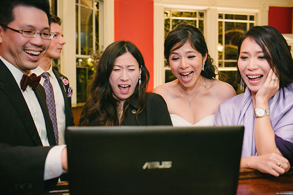 Bride chatting via live stream video with guests who couldn't attend her international San Francisco wedding by destination wedding planner Mango Muse Events