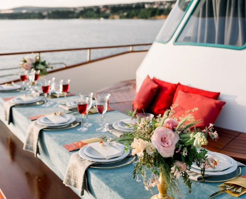 Elegant and fun red and teal tablescape for a wedding reception on a yacht in Croatia by destination wedding planner Mango Muse Events