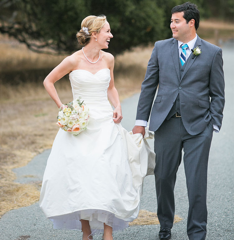 Groom holding bride's dress at a Carmel wedding by wedding planning pro Mango Muse Events