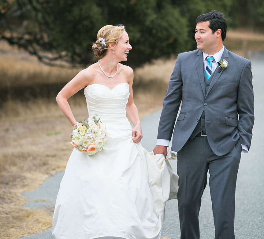 Groom holding bride's dress at a Carmel wedding by destination wedding planner Mango Muse Events