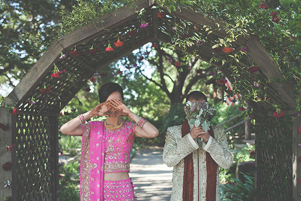 Bride and groom standing under an arch in traditional Indian wedding attire covering their faces at a multicultural wedding at the Los Altos History Museum by Bay Area based destination wedding planner Mango Muse Events