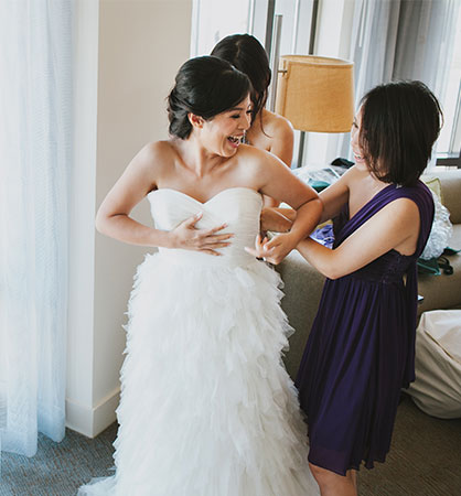 Happy bride putting on her dress with the help of friends at her San Francisco destination wedding by destination wedding planner Mango Muse Events founder of Let's I do this! virtual weddings