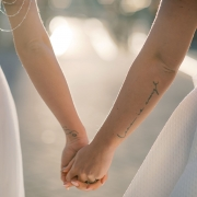 Two brides holding hands with love is enough tattoo at their same sex wedding in Amsterdam by destination wedding planner Mango Muse Events