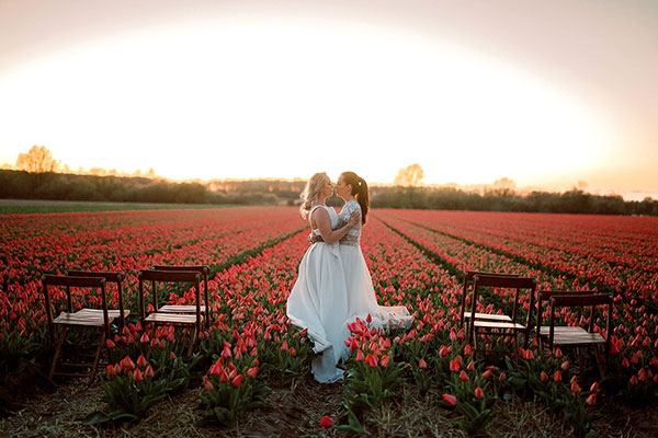 Two brides embracing at their sunset wedding in the tulip fields in the Netherlands by destination wedding planner Mango Muse Events