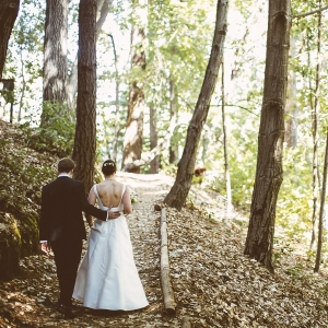 Bride and groom walking in the forest at their woodland wedding in Ben Lomond near Santa Cruz by destination wedding planner Mango Muse Events