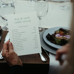 Guest holding wedding trivia game at a wedding reception in Yosemite by destination wedding planner Mango Muse Events