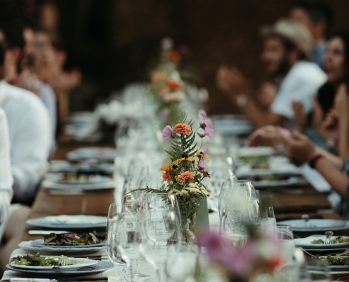 Boho wild flower centerpieces and mis-matched china at long tables for a wedding reception in Yosemite by destination wedding planner Mango Muse Events