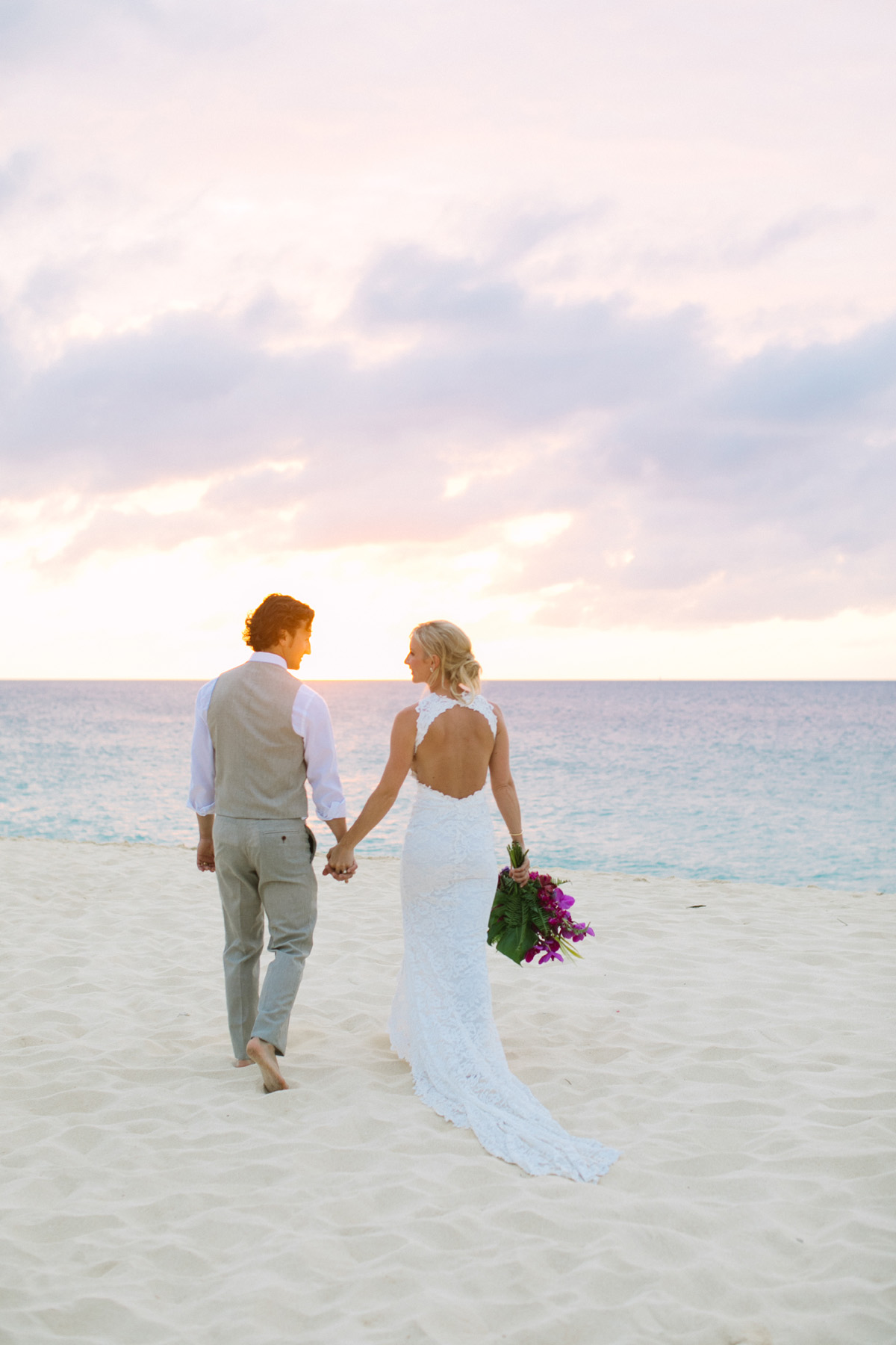 Bride and groom holding hands at their sunset wedding on the beach in Anguilla Caribbean by destination wedding planner Mango Muse Events