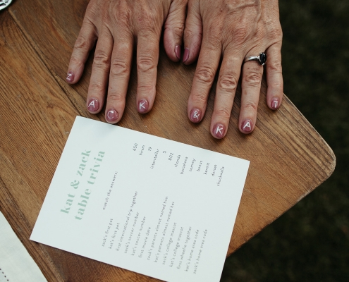Fun wedding trivia game at tables with a guest's fun nail design by destination wedding planner Mango Muse Events