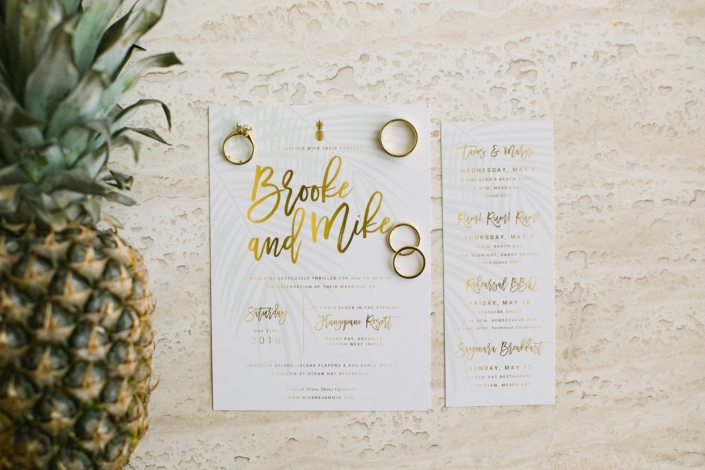 Gold script wedding invitation wedding rings and pineapple for a tropical wedding in Anguilla by destination wedding planner Mango Muse Events