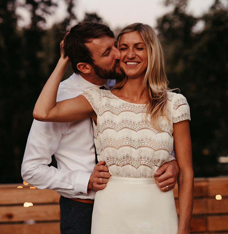 Happy couple cheek kiss moment Yosemite mountain wedding by destination wedding planner Mango Muse Events