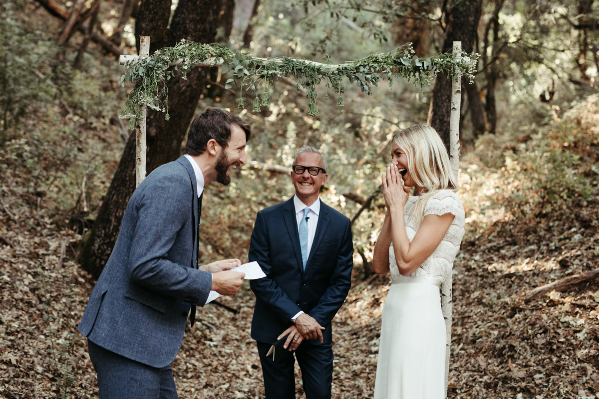 Happy couple laughing during personal vows at their wedding ceremony in Yosemite by destination wedding planner Mango Muse Events
