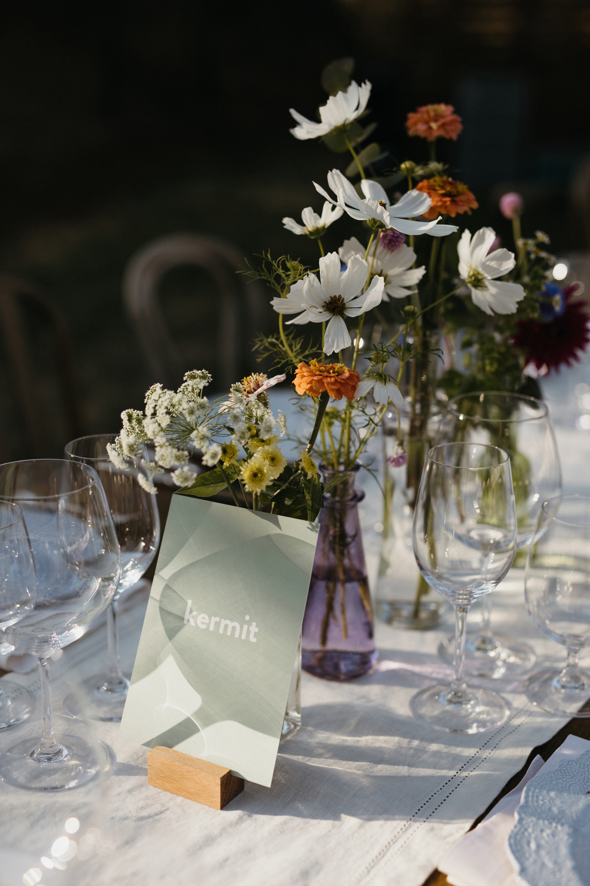 Locally grown wild flower centerpieces and trivia table names at a boho Yosemite wedding by destination wedding planner Mango Muse Events