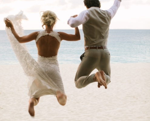 Newlyweds jumping for joy at their beach wedding in Anguilla Caribbean by destination wedding planner Mango Muse Events