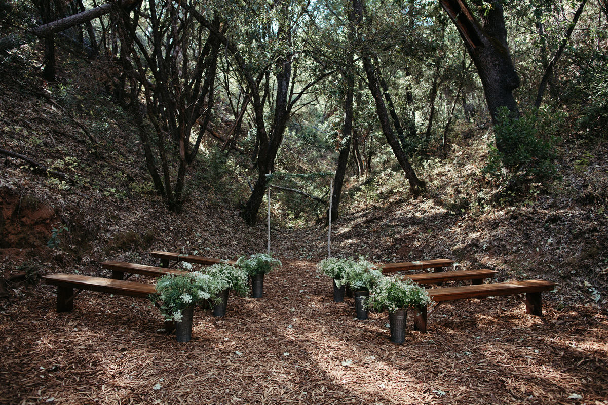 Private and intimate micro wedding ceremony benches and white wild flower bushels at a Autocamp Yosemite wedding by destination wedding planner Mango Muse Events