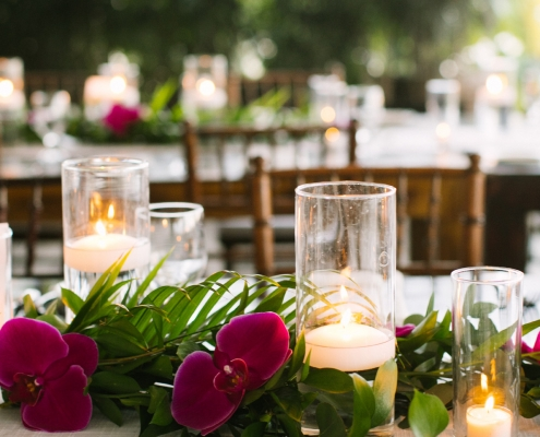 Tropical leaves, purple orchids and floating candle centerpieces for a Anguilla Caribbean wedding reception at Straw Hat restaurant by destination wedding planner Mango Muse Events