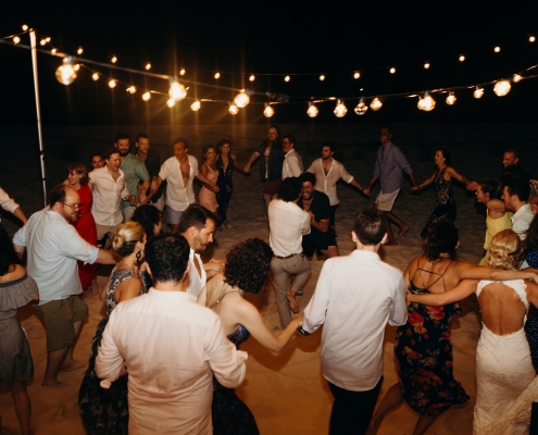 Wedding guests dancing the hora on the beach at an Anguilla Caribbean wedding by destination wedding planner Mango Muse Events
