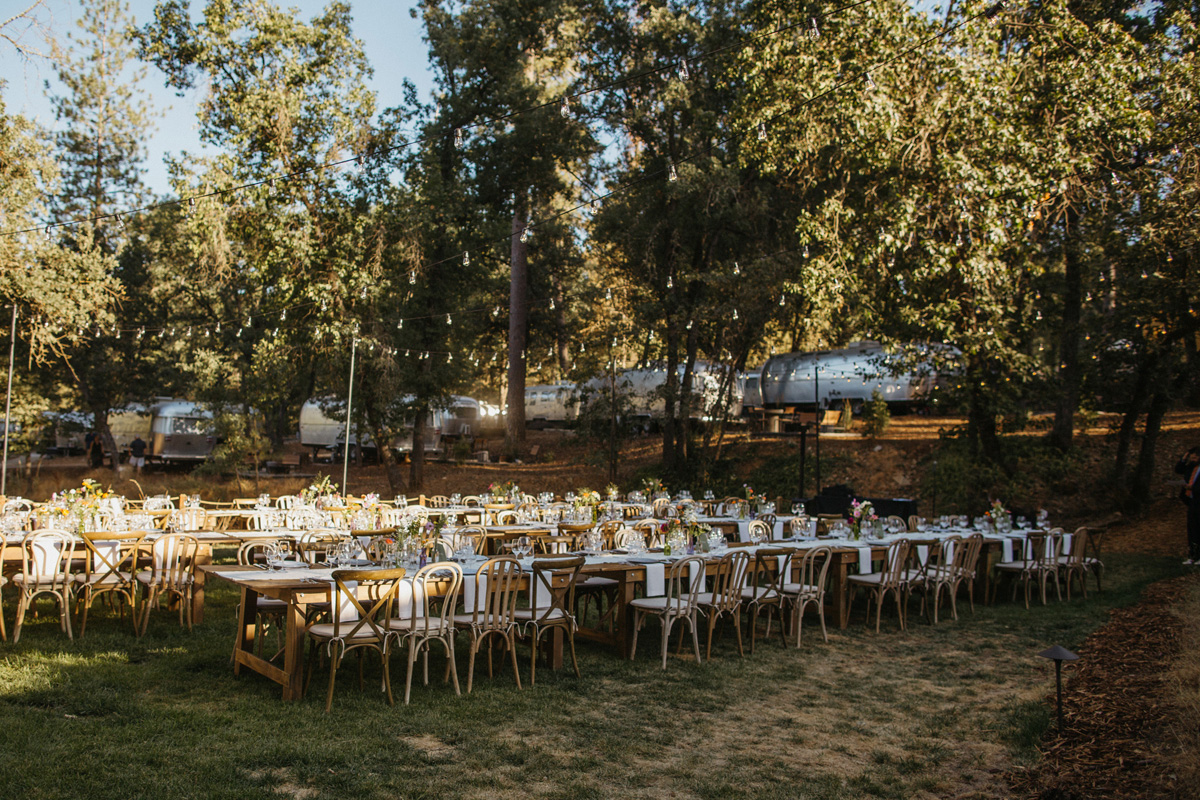 Wedding reception long tables with glamping airstreams at a wedding at Autocamp Yosemite by destination wedding planner Mango Muse Events