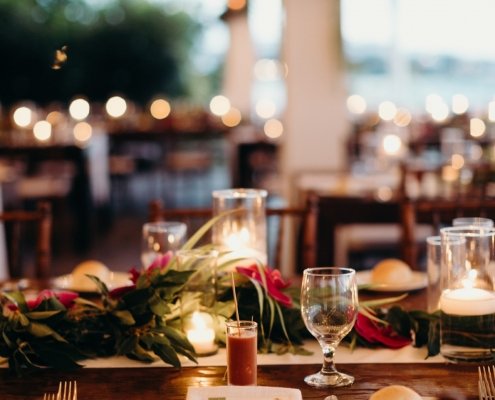 Wedding reception tablescape with candles and tropical garland centerpiece at a Anguilla Caribbean wedding reception at Straw Hat restaurant by destination wedding planner Mango Muse Events