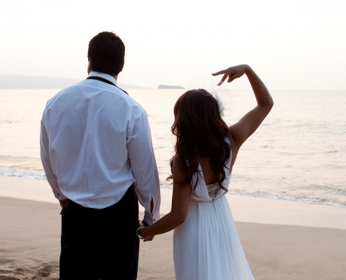 Bride and groom at their sunset beach wedding making the peace sign by destination wedding planner Mango Muse Events