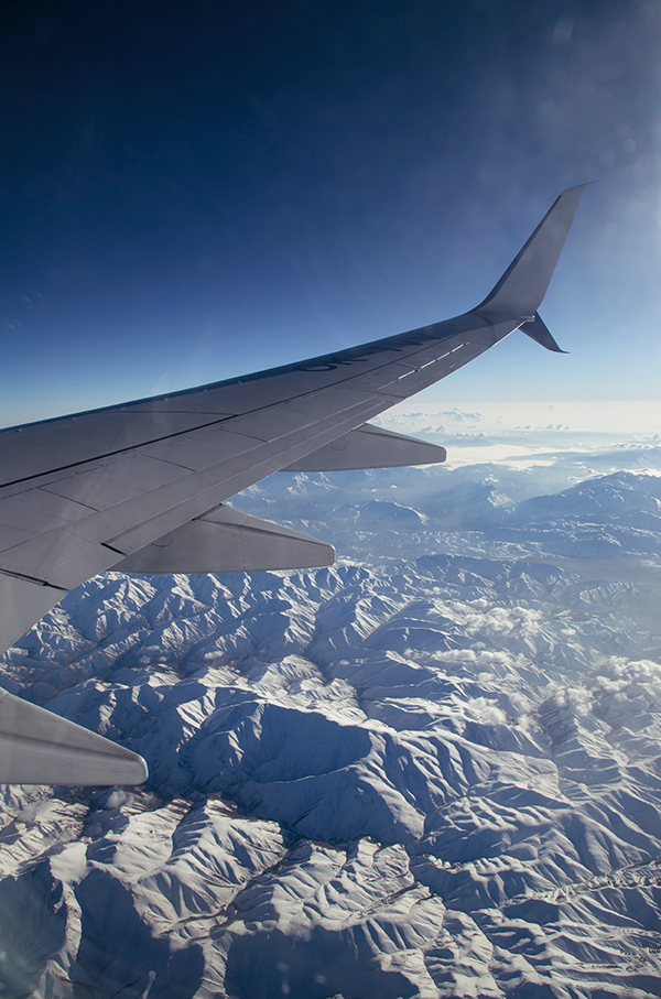 Airplane wing flying over mountains for a wedding by destination wedding planner Mango Muse Events