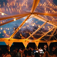 Clear wedding reception tent with glowing bistro lights at a destination wedding in Hawaii by destination wedding planner Mango Muse Events
