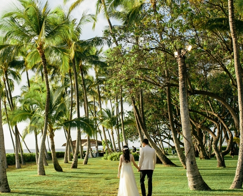 Bride and groom walking at their wedding amoungst the palm trees at a private estate wedding in Hawaii at Lanikuhonua by destination wedding planner Mango Muse Events