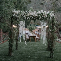 Elegant floral grand entrance to the wedding reception on the lawn at Calistoga Ranch by destination wedding planner Mango Muse Events