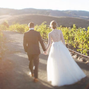 Bride and groom taking a romantic stroll in the vineyards at their Sonoma wine country wedding by Destination wedding planner Mango Muse Events