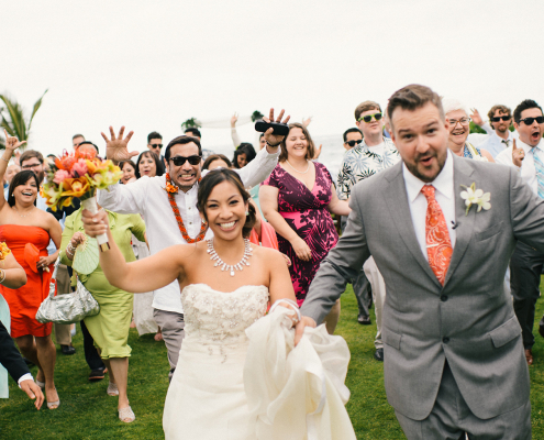 Wedding guests running and excited after the ceremony at a Hawaii destination wedding by destination wedding planner Mango Muse Events