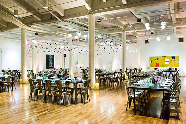 Hanging flowers and artsy cool wedding reception at Terra Gallery in San Francisco by destination wedding planner Mango Muse Events