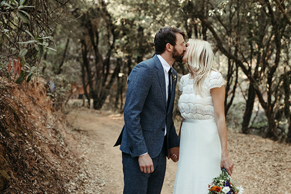 Bride and groom kiss after the wedding ceremony at their forest wedding at Autocamp Yosemite by destination wedding planner Mango Muse Events