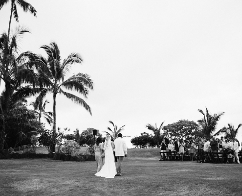 Bride walking down the aisle at an outdoor private estate wedding at Loulu Palm in Hawaii by destination wedding planner Mango Muse Events