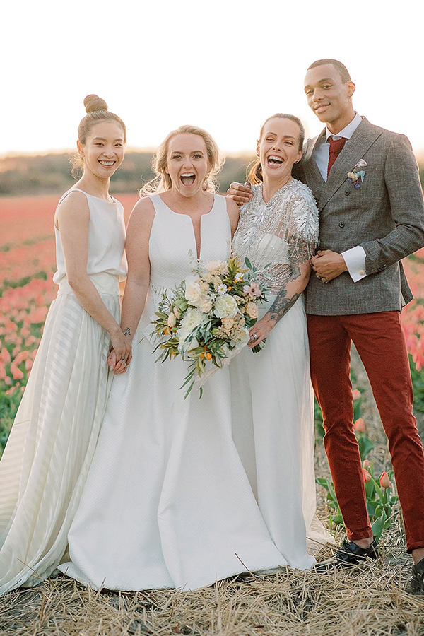 Happy lesbian couple and their mixed wedding party in the tulip fields at their Amsterdam wedding by destination wedding planner Mango Muse Events