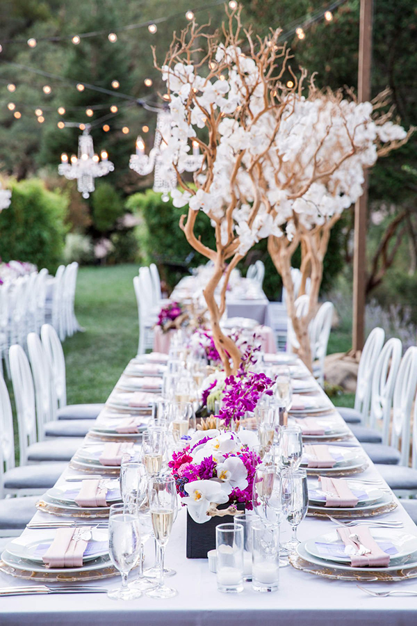 Lush elegant wedding table with purple flowers and branches hanging chandeliers at a Calistoga Ranch wine country wedding by destination wedding planner Mango Muse Events